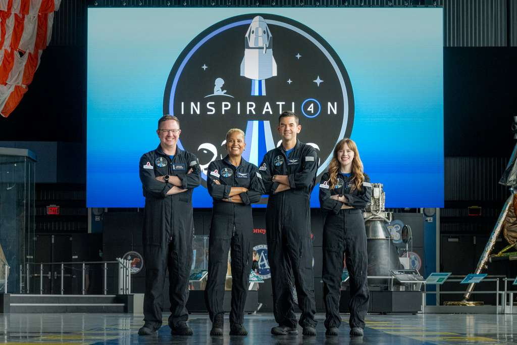 Les membres de la première mission mondiale entièrement civile dans l'espace pose devant l'écusson d'Inspiration4. © Inspiration4, John Kraus