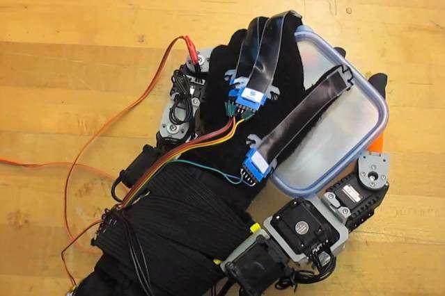 Sur cette image, on voit comment le système permet sa saisir une boîte avec les deux doigts robotisés tout en l'ouvrant avec la même main. Une fois miniaturisé, cet équipement pourrait notamment servir aux personnes âgées ou handicapées, ou pourquoi pas dans certaines industries. © Melanie Gonick, Massachusetts Institute of Technology