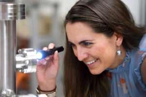 La chercheuse Sarah Hörst vérifie grâce à une lampe s'il y la formation de brume dans l'enceinte où se déroule l'expérience. © Will Kirk/JHU
