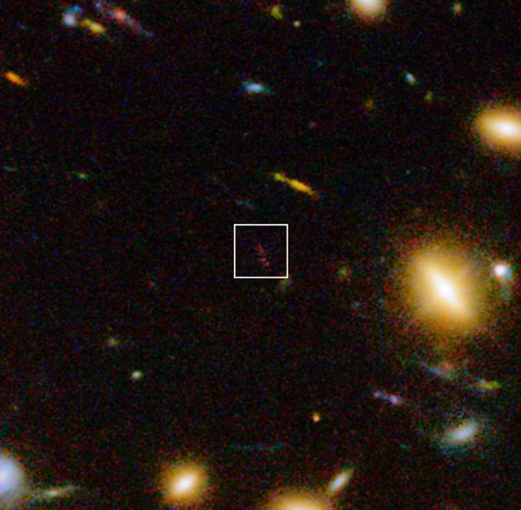 Sur cette image acquise dans le visible et l'infrarouge avec la caméra WFC3 d'Hubble, gros plan dans l'amas galactique Abell 1689 sur l'objet A1689-zD1 situé à un peu plus de 13 milliards d'années-lumière de notre galaxie, la Voie lactée. Les nouvelles observations effectuées au moyen d'Alma et du VLT ont montré qu'il s'agit d'une galaxie poussiéreuse qui nous apparaît telle qu'elle était lorsque l'univers était âgé d'environ 700 millions d'années. © Eso, J. Richard