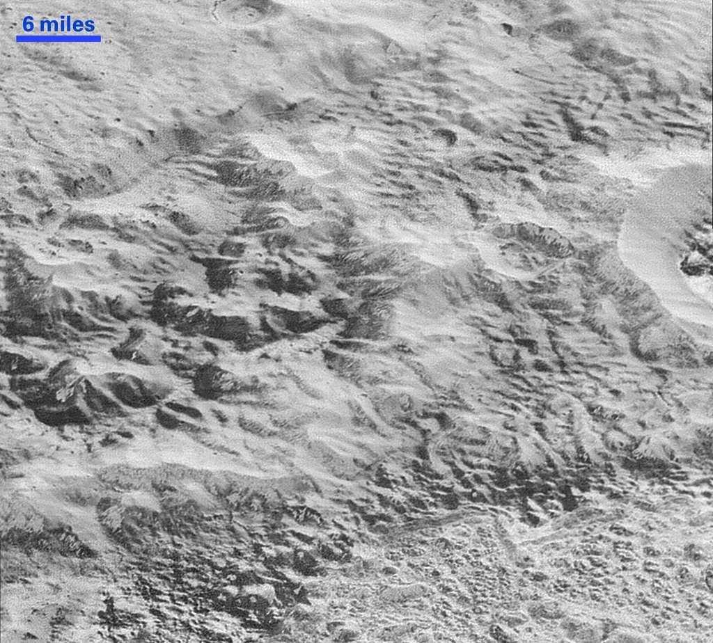Une image d'une région de Pluton faisant penser aux badlands sur Terre. La barre en haut à gauche donne l'échelle qui est d'environ 9,6 kilomètres (6 miles). La largeur de l'image est d'environ 80 kilomètres. © Nasa, JHUAPL, SwRI