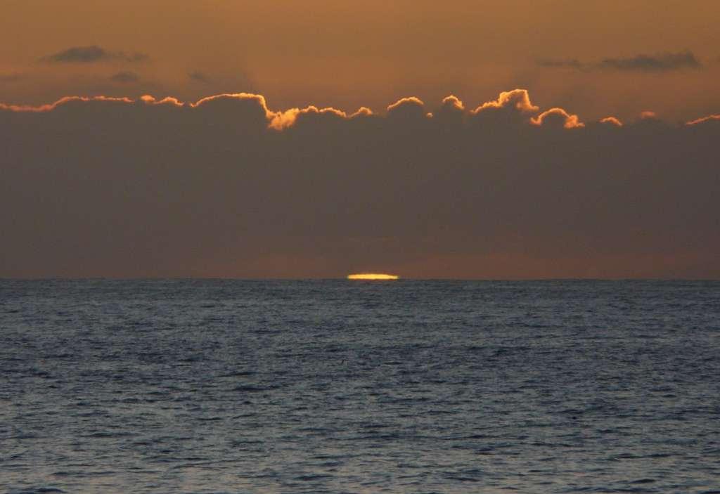 Le Soleil plonge dans la mer. Avant sa disparition complète la diffraction commence à faire virer au vert la bordure du disque la plus proche de l'horizon. Crédit J-B Feldmann