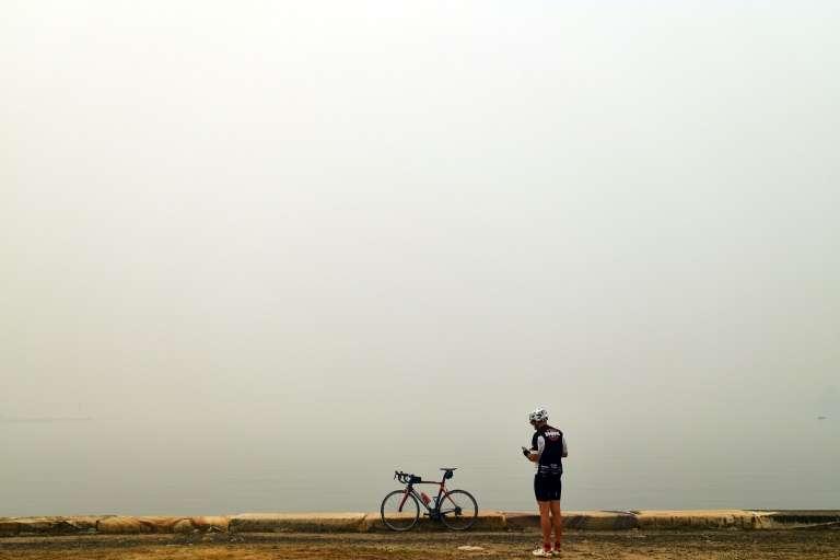 Un cycliste observe la fumée toxique à Gosford (Australie) le 10 décembre 2019. © Saeed Khan, AFP