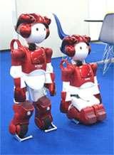 Emiew 2 au repos. A gauche, les barres stabilisatrices, au niveau des pieds, sont abaissées et les roulettes immobilisées. Mais il peut aussi s'agenouiller. © Hitachi