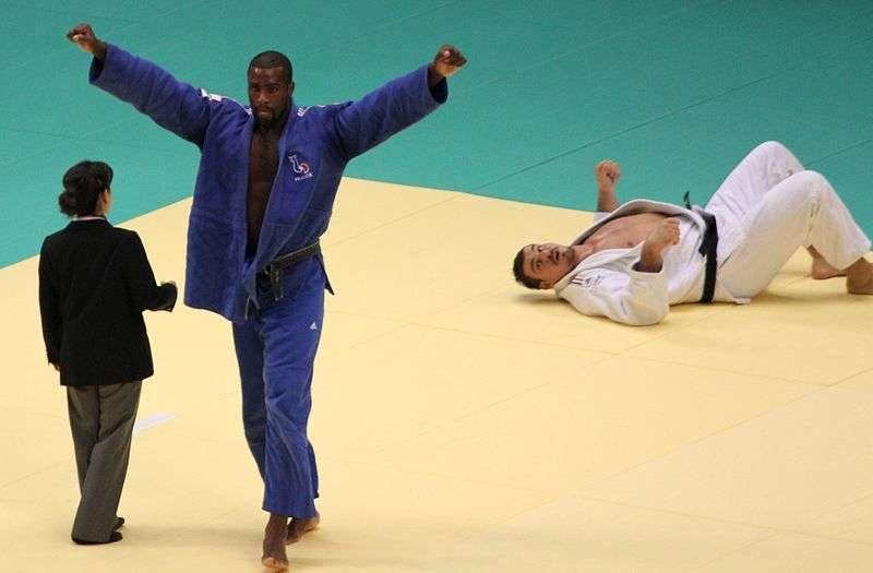 Le judoka français Teddy Riner, ici en kimono bleu, lève les bras après avoir mis son adversaire allemand Andreas Tölzer à terre et remporté le titre de champion du monde des poids lourds. Cette célébration du succès, considérée comme une marque de domination, serait universelle plutôt que culturelle. © XIIIfrom TOKYO, Wikipédia, cc by sa 3.0