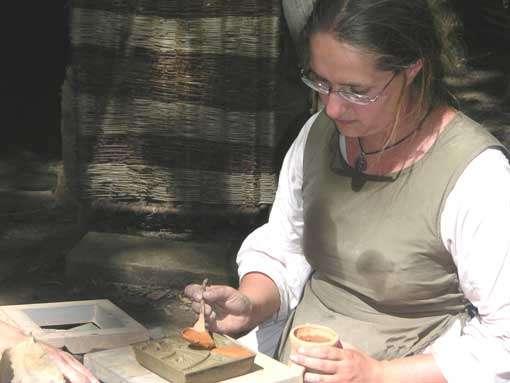La tuilière en train de réaliser un carreau de pavement. Les carreaux et tuiles sont réalisés avec l'argile extraite du chantier. © Guédelon - Reproduction et utilisation interdites - Tous droits réservés