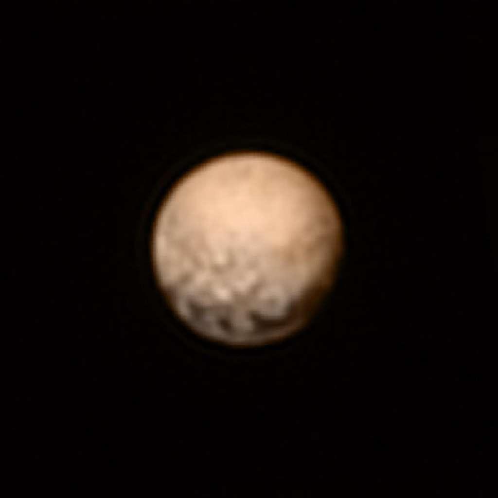 Image en couleurs de Pluton créée à partir de celle prise par le télescope Lorri de New Horizons, associée aux données obtenues avec l'instrument Ralph, quelques jours auparavant. Les grandes taches sombres visibles en bas chevauchent l'équateur de la planète naine. De nouveaux détails sont apparus au-dessus de cette région, à mesure que la sonde se rapproche. Des images à comparer avec celles d'Hubble réalisées en 2010. © Nasa, JHUAPL, SwRI