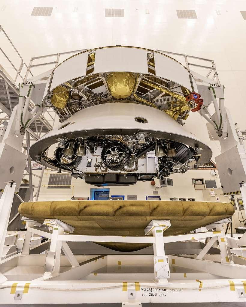 Le rover Perseverance installé dans son bouclier thermique (aeroshell, en anglais) qui se compose d'un cône arrière (backshell) et d'un cône avant (heatshield). Le cône arrière (de couleur blanche) est surmonté de l'étage de croisière utilisé pour le voyage entre la Terre et Mars. © Nasa, Christian Mangano