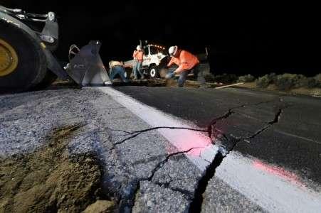 Des ouvriers comblent un trou ouvert sur une route près de Ridgecrest en Californie, après un séisme de magnitude 7,1, le plus important depuis 20 ans. © Robyn Beck, AFP