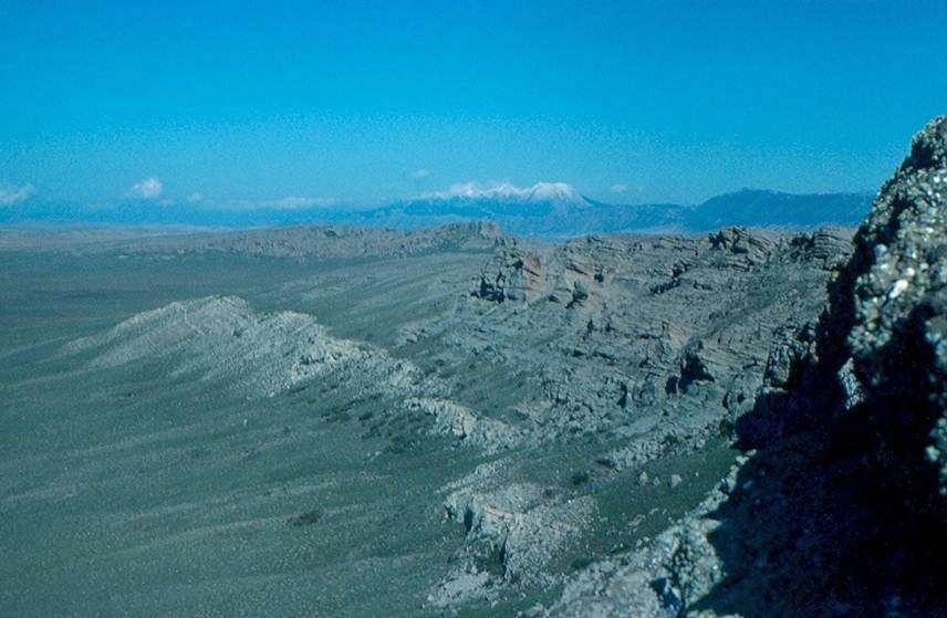 Ci-dessus, une partie de l'anneau pyroclastique du maar de Bou Ibalrhatene dans le Moyen-Atlas (Maroc). Chacune des couches du croissant résulte des retombées d'une explosion : la structure bréchique est bien visible à droite de la photographie. Les formations inférieures blanches sont des calcaires jurassiques. Les éléments du croissant pyroclastique sont, outre les calcaires, des fragments de granite hercynien, des péridotites et des pyroxénites à grenat du manteau supérieur. © Jacques Kornprobst