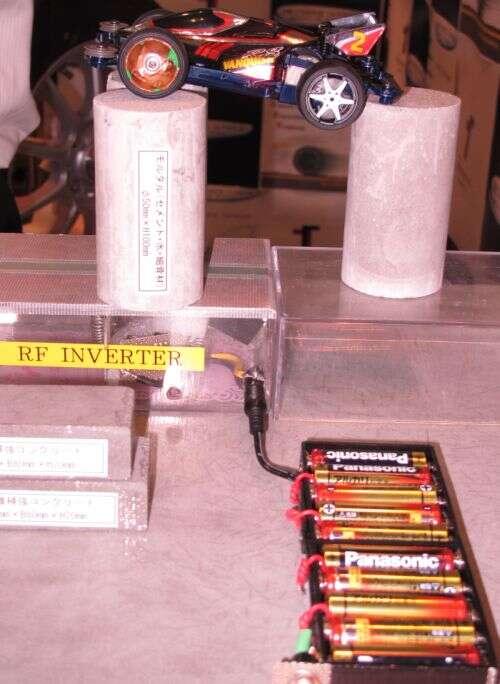 Il n'existe aucun lien matériel entre les piles et la voiture. Les chercheurs sont pourtant parvenus à faire tourner les roues de ce modèle réduit tandis qu'il était posé sur des plots en béton de 10 cm de hauteur. Le RF Inverter est chargé de transmettre de l'électricité par des signaux radio, grâce à un système par induction, aux récepteurs que sont les pneus. © Tech-On