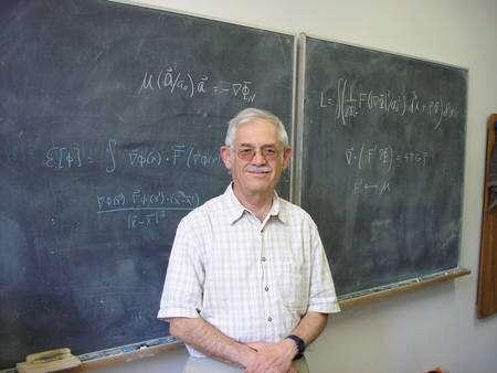Cliquer pour agrandir. Jacob Bekenstein devant des équations de la théorie Mond. Crédit : Wikipedia Commons