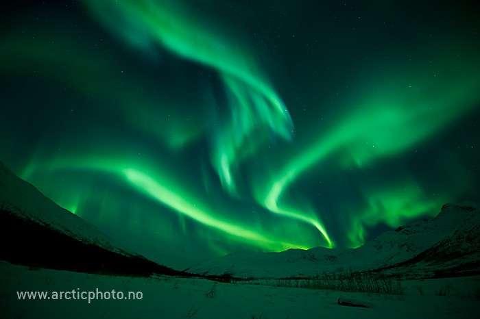 Aurore boréale au-dessus de sommets enneigés. © Bjørn Jørgensen