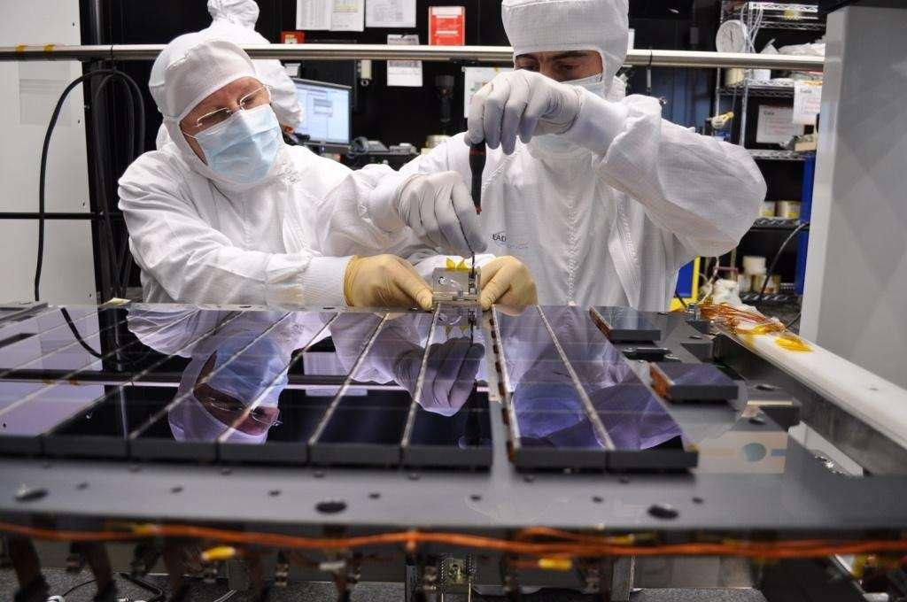 Des techniciens en train de monter les capteurs CCD de Gaia dans une chambre blanche à Toulouse. Il y en a 106 au total et il fallait en moyenne une journée pour en installer 4. Les éléments sont sur des supports en carbure de silicium et l'ensemble pèse 20 kg. Chaque capteur CCD mesure 6 × 4,7 cm, avec une épaisseur de seulement quelques dizaines de microns. L'écart entre les CCD adjacentes est d'environ 1 mm. © Astrium