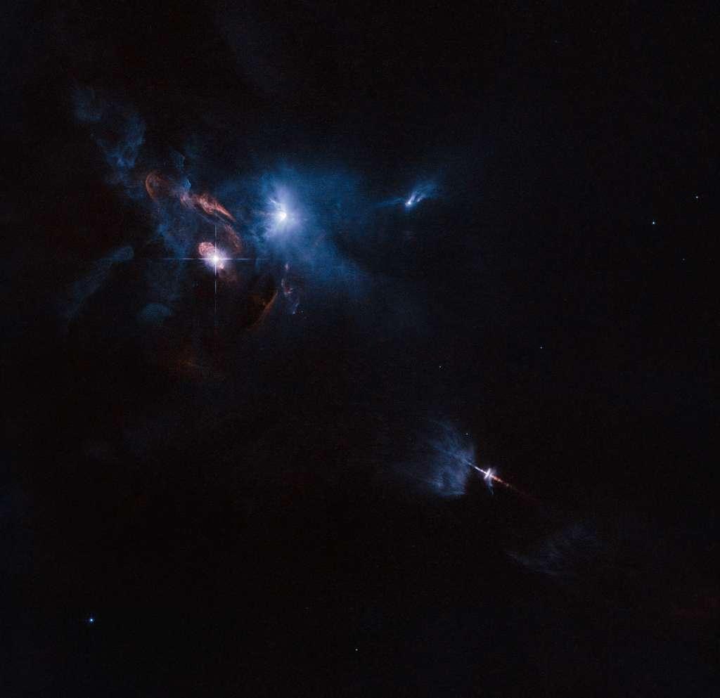 Sur cette image réalisée par le télescope spatial Hubble, on découvre l'environnement tumultueux de HL-Tauri (au sein du nuage bleuté), très jeune étoile indiscernable dans le visible, entourée d'un disque protoplanétaire. © Esa, Nasa, Hubble, Judy Schmidt