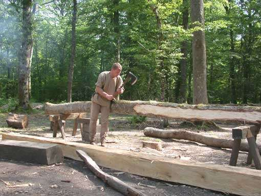Essarteur en train d'équarrir un fût de chêne. Le tronc une fois équarri sera transporté chez les charpentiers pour y être façonné. © Guédelon - Reproduction et utilisation interdites - Tous droits réservés
