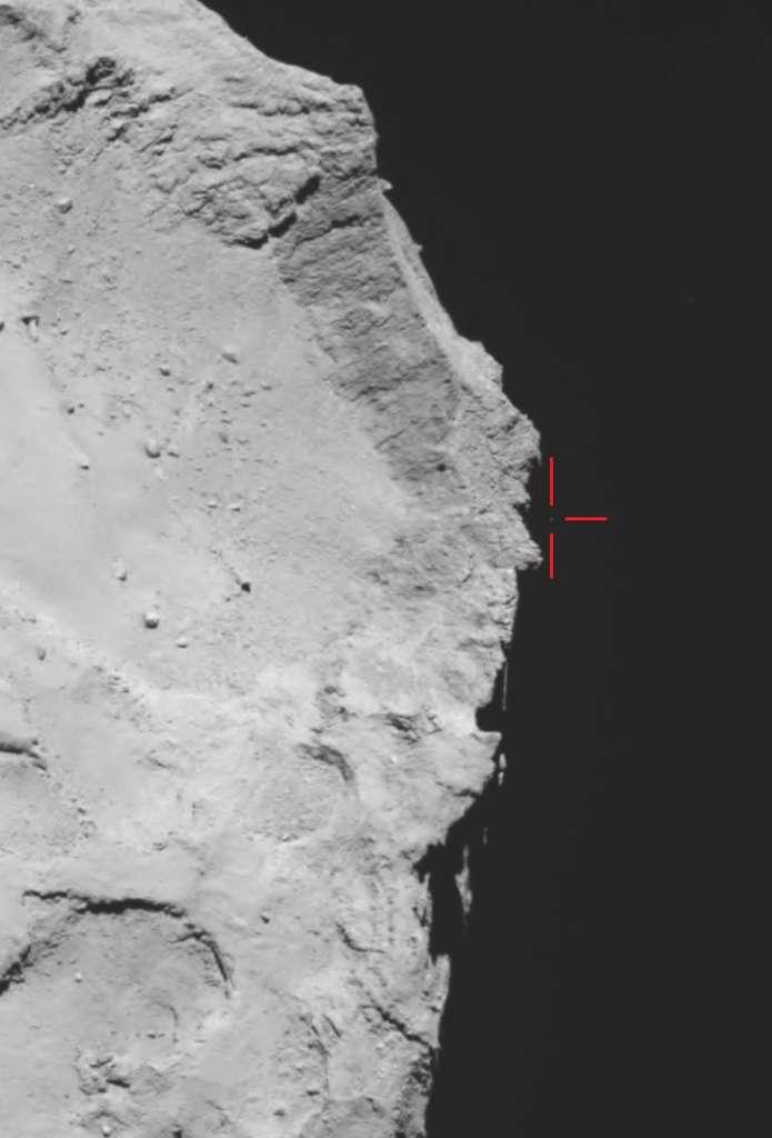 Il était 17 h 18 TU, le 12 novembre 2014, lorsque la caméra grand-angle d'Osiris a réalisé cette photo. Les scientifiques pensent que le petit point gris (3 pixels) que l'on aperçoit sur le limbe de la comète, au-dessus des remparts qui bordent la dépression Hatmehit, pointé par les traits rouges, est peut-être Philae. © Esa, Rosetta, MPS, UPD, LAM, IAA, SSO, INTA, UPM, DASP, IDA