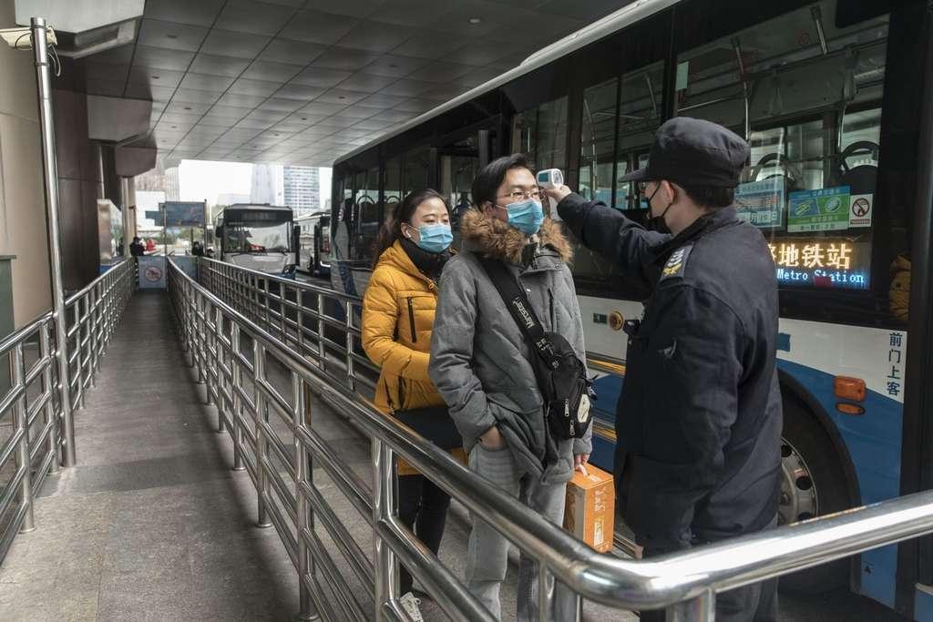 Un agent officiel contrôle la température des voyageurs avant de prendre le bus. © Bloomberg