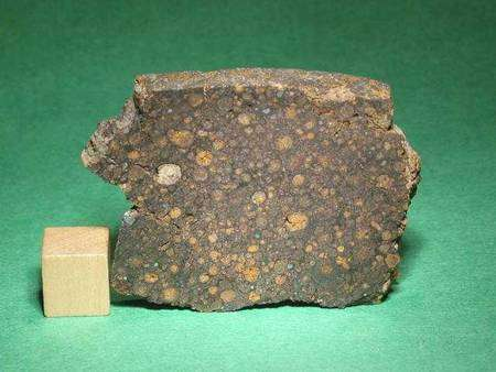 Un exemple de chondrite CR. Le cube de bois mesure un centimètre de côté. © The Meteorite Market
