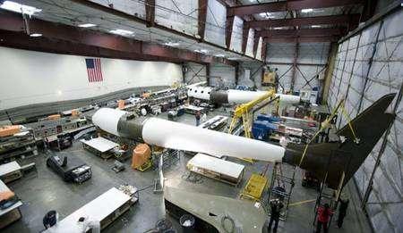L'avion porteur WhiteKnightTwo en cours d'assemblage. A gauche, contre le flanc du hangar, on remarque l'aile de l'appareil. Crédit Virgin Galactic.