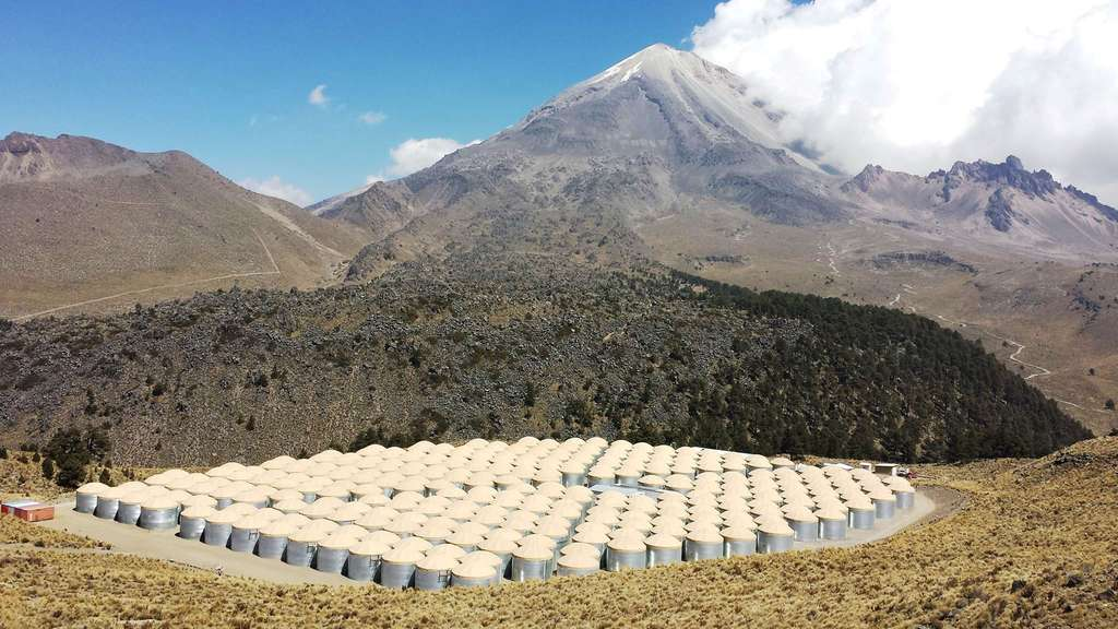 Une vue de l'observatoire High Altitude Water Cherenkov situé à plus de 4.000 mètres d'altitude sur les pentes d'un volcan mexicain. Les 300 réservoirs contiennent de l'eau très pure et des détecteurs de rayonnement Cherenkov, une sorte de « bang » lumineux qui se produit dans l'eau au passage de particules chargées très rapides. © HAWC Collaboration, Samuel Marinelli