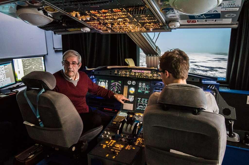 Dans son simulateur de A320, Gérard Gaillard donne une leçon de travaux pratiques aux futurs ingénieurs de l'air, ici le doigt pointé sur un instrument de radionavigation « à l'ancienne ». © Ipsa