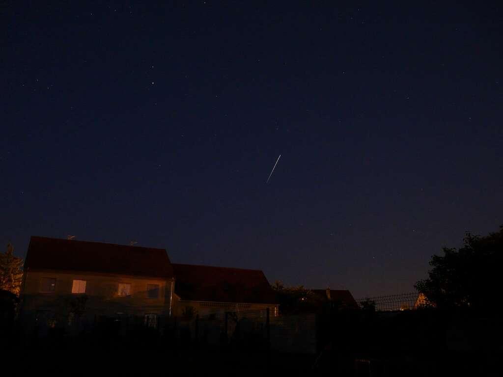 Sur ce cliché pris au crépuscule, la Station Spatiale Internationale a laissé un tiret lumineux en raison de son déplacement pendant les 10 secondes qu'a duré la pose. Crédit J.-B. Feldmann