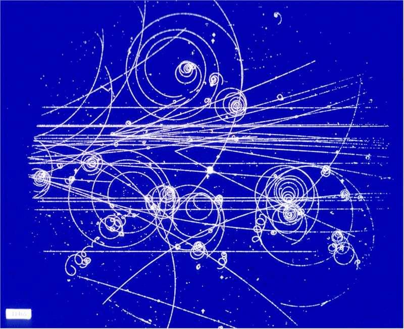Une image prise dans une chambre à bulles montrant les trajectoires des particules courbées par un champ magnétique. Le sens de la courbure donne le signe de la charge de la particule, et le rayon de courbure mesure la quantité de mouvement. © Cern