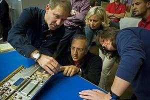 Mike Massimino (accroupi) à côté de l'astronaute John Grunsfeld (à gauche de l'image), avec l'équipe d'ingénieurs, en train d'étudier un modèle de test du spectromètre STIS, qui doit être réparé lors de la prochaine mission de maintenance, initialement prévue en octobre 2008. © Nasa