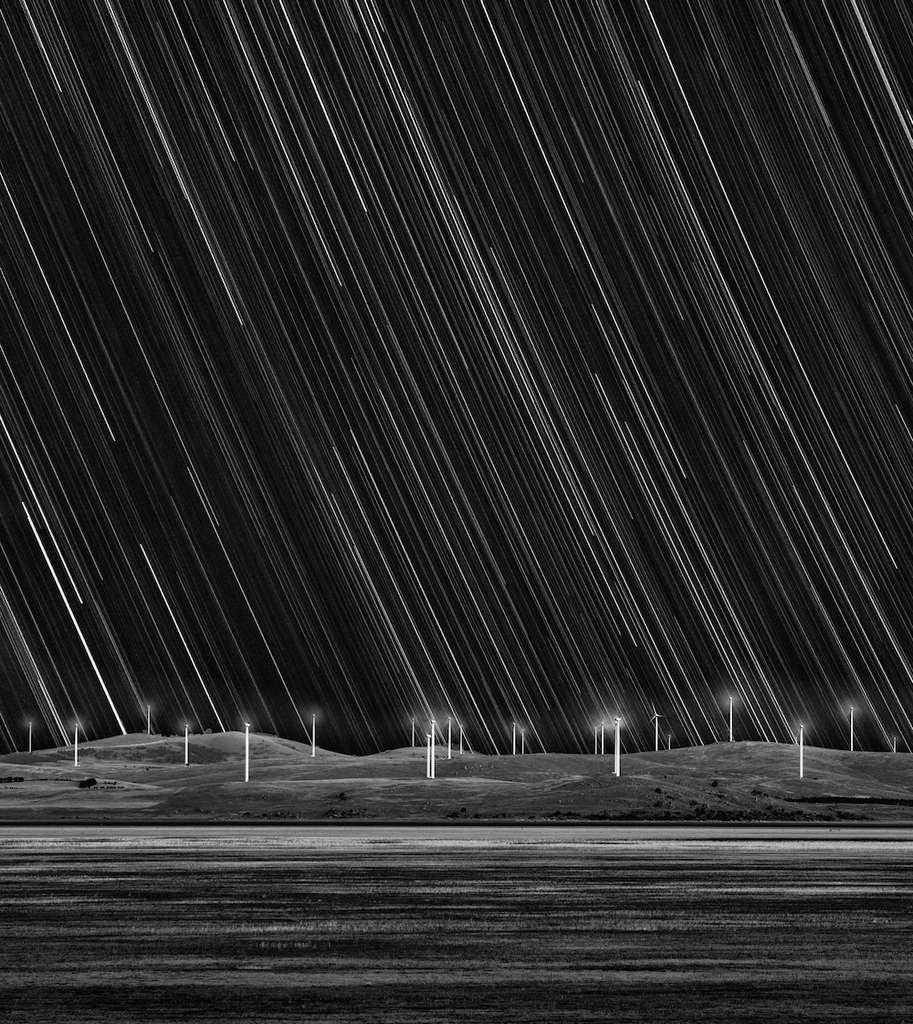 Trainées d'étoiles au-dessus d'une ferme d'éoliennes