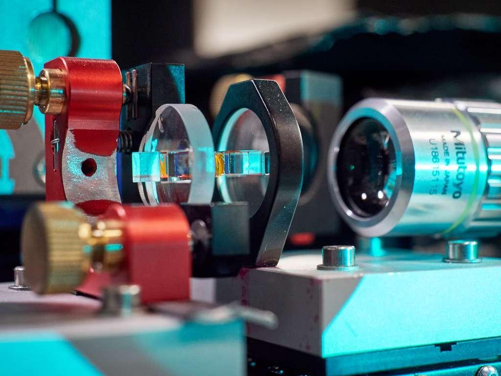 Le microrésonateur optique utilisé dans leur expérience par les chercheurs de l'université de Bonn (Allemagne). En jaune, on devine le colorant qui refroidit les photons. Et à droite, un microscope pour observer la lumière émise. © Gregor Hübl, Université de Bonn