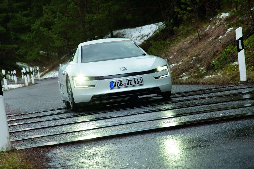 La XL1 roule. Surbaissée (1,15 m de hauteur), elle est propulsée (ce n'est pas une traction) par un moteur placé à l'arrière. Hybride, la motorisation est composée d'un bicylindre Diesel de 0,8 L de cylindrée et d'un moteur électrique de 20 kW, dont les batteries sont situées à l'avant. © Volkswagen