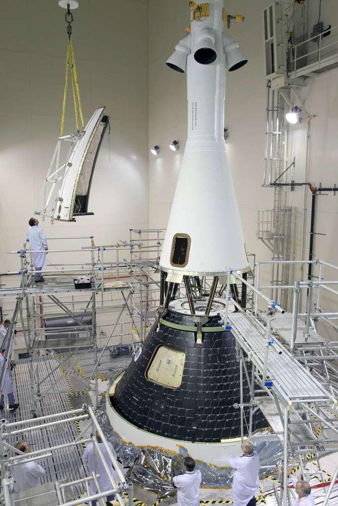 Mise sous coiffe de la capsule Orion au-dessus de laquelle on peut voir comment est fixée la tour de sauvetage de l'engin. Cette dernière est utilisée en cas de problème grave sur le lanceur pour éloigner le plus rapidement possible la partie habitable d'Orion. © Nasa