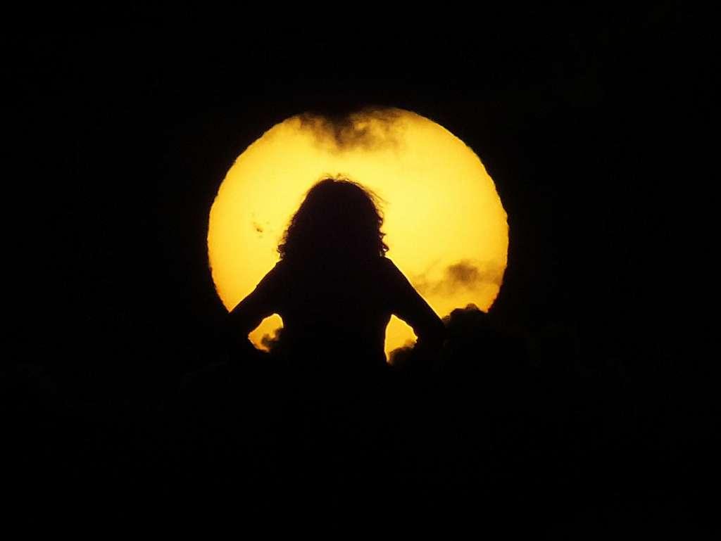 Le 9 juillet au coucher du Soleil une admiratrice contemple notre étoile ; à sa gauche se déploie la nouvelle tache solaire géante AR 1520. © Jean-Baptiste Feldmann
