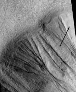 Sur la gauche de l'image des ravines déjà formées, à l'extrême droite, une plaque de neige (flèche)