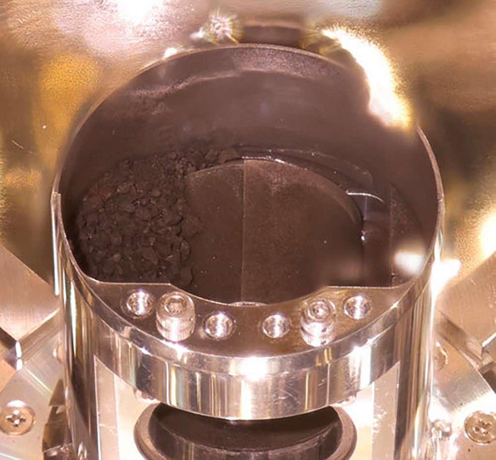 L'ouverture du récipient, dans lequel les échantillons de Ryugu ont été récoltés, montre ce qui a été récupéré sur la surface de l'astéroïde. On peut voir plein de grains assez gros et très noirs, mais aussi avec quelques petits points blancs. Ne vous fiez pas à l'image qui laisse à penser qu'il s'agit de petits cailloux. Le diamètre du conteneur est de... 48 millimètres (moins de cinq centimètres) ! © Jaxa