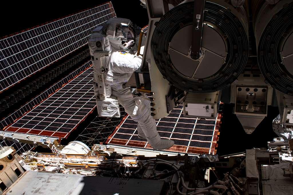 Shane Kimbrough lors de la sortie extravéhiculaire le 16 juin 2021 qui s'affaire autour du premier iROSA dont ont peut voir qu'il est roulé sur lui-même en deux cylindres repliés l'un sur l'autre. Et non, l'astronaute américain ne « marche » pas sur les panneaux solaires actuellement en service. © Nasa