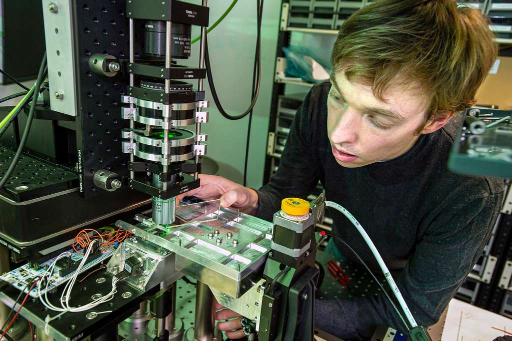A Microsoft optical scientist is loading a piece of glass into a system using optics and artificial intelligence to extract and read data stored on glass.  © Jonathan Banks, Microsoft.
