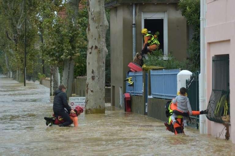 Des pompiers évacuent des personnes dans une zone inondée de Trèbes, près de Carcassonne, le 15 octobre 2018 dans l'Aude. © Pascal PAVANI, AFP