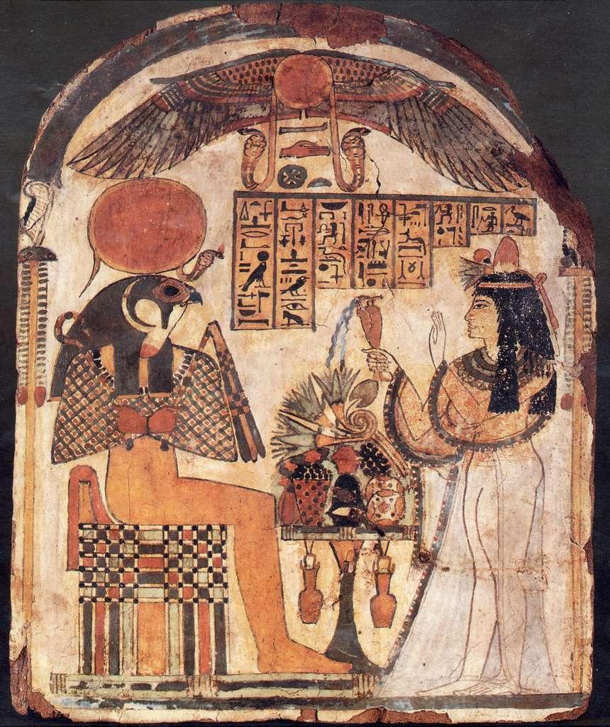 Le dieu Râ, ici incarné par un homme à tête de faucon, reçoit des offrandes de nourriture, de boissons et de fleurs. Stèle en bois à l'Institut d'Orient de l'université de Chicago. © Wikimedia Commons, DP