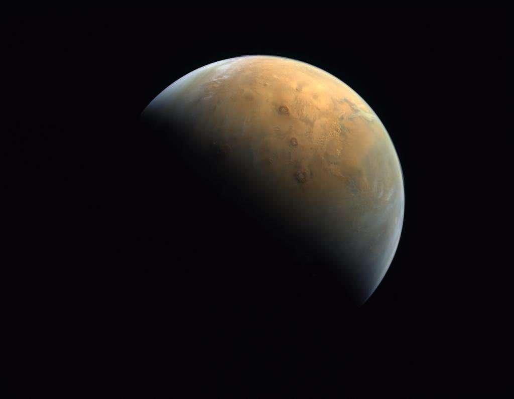 Première photo de Mars prise par la sonde Hope à 25.000 kilomètres au-dessus de la surface de la planète rouge. On distingue les trois volcans alignés des monts Tharsis. © MRSBC