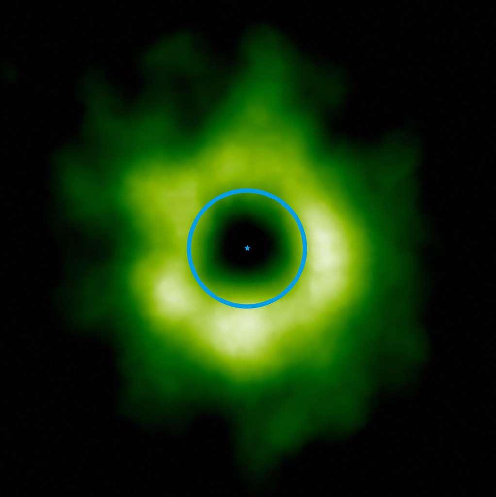 Cette image prise par Alma montre en fausses couleurs (teintes vertes) la région où le monoxyde de carbone est présent à l'état de glace autour de l'étoile TW Hydrae (indiqué au centre). À titre d'échelle, le cercle bleu symbolise l'orbite de Neptune autour du Soleil. La transition vers la glace de monoxyde de carbone pourrait aussi marquer la limite intérieure de la zone où se forment les petits corps glacés, tels que les comètes et les planètes naines comme Pluton et Éris. © ESO