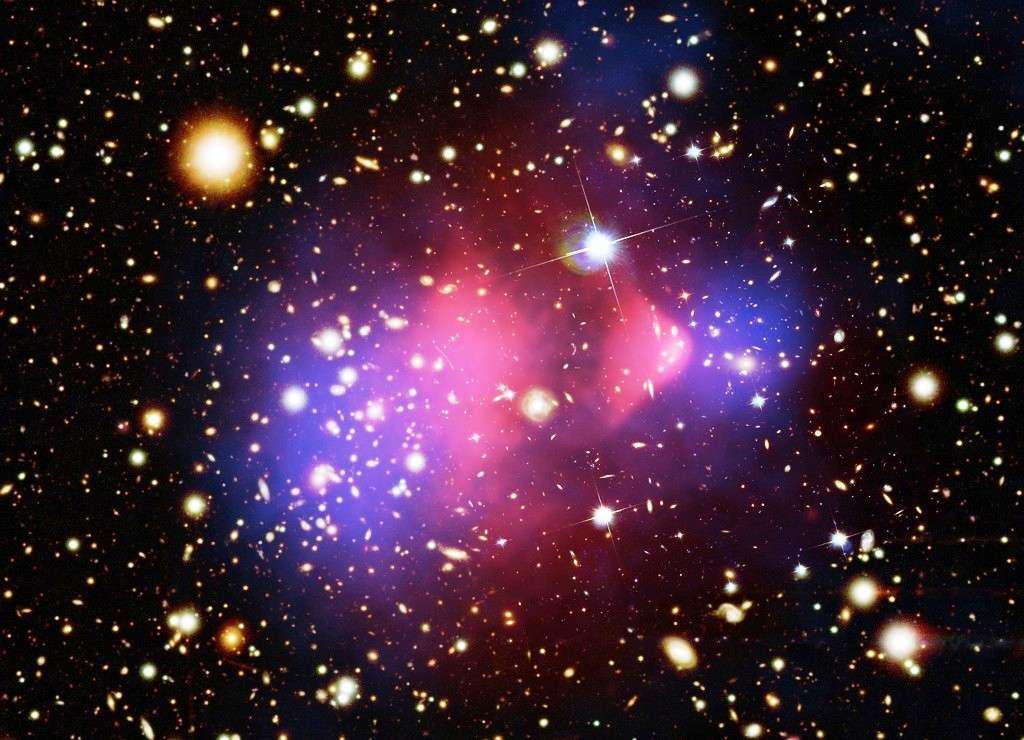 La matière noire forme un halo qui entoure chaque amas galaxie. Ici la collision de deux amas (le bullet cluster) montre comment les halos (en bleu) s'interpénètrent sans interagir, alors que le gaz de matière normal (en rouge) interagit et donc se retrouve décalé. Crédits : rayons XNASA/CXC/CfA/ M.Markevitch et al.; lentille gravitationnelle : NASA/STScI; ESO WFI; Magellan/U.Arizona/ D.Clowe et al. Visible : NASA/STScI; Magellan/U.Arizona/D.Clowe et al.