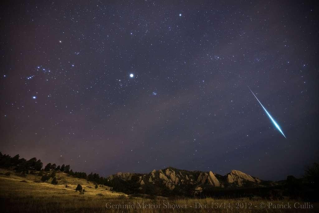 Une brillante Géminide (on peut comparer son éclat à celui de Jupiter, au centre de l'image) survole les Flatirons, des formations rocheuses dans le Colorado. © Patrick Cullis