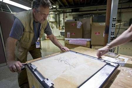 Le paléontologue Peter Larson préparant le fossile d'archéoptéryx pour l'examen. © SLAC National Accelerator Laboratory