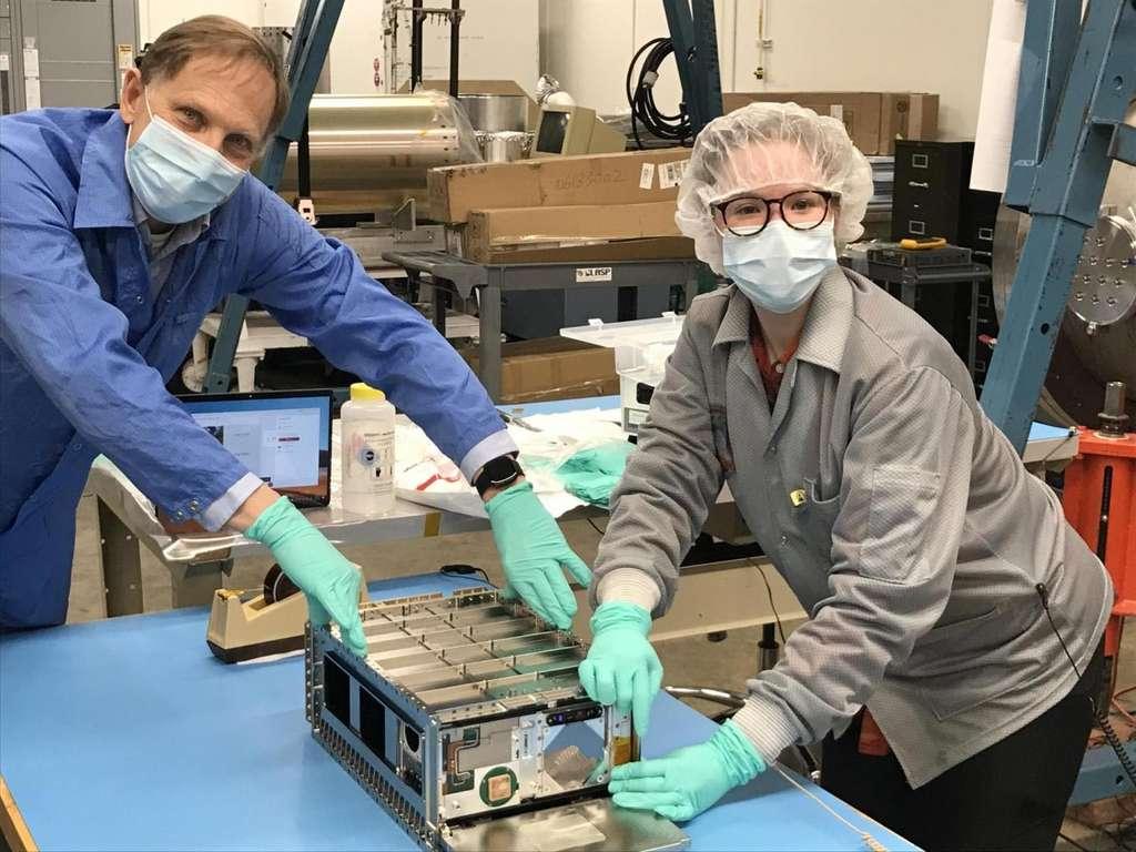 Rick Kohnert, ingénieur système pour Cute, et Arika Egan, étudiante au Laboratoire de physique atmosphérique et spatiale qui a aidé à développer la mission, posent avec le petit satellite au LASP. © Kévin France.