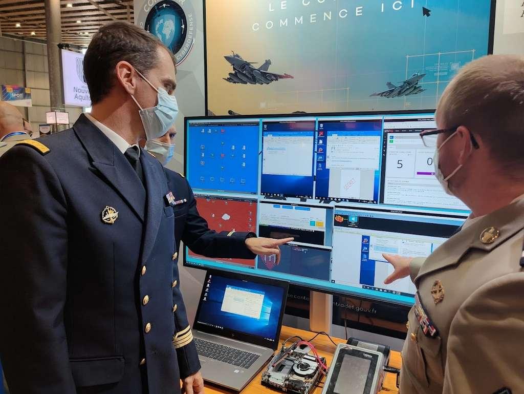 Sur le salon du FIC à Lille, l'adjudant Sébastien présente au capitaine de corvette Xavier le Trident, un caisson d'entraînement à la cyberdéfense d'un réseau équivalent à celui d'une PME. © Futura