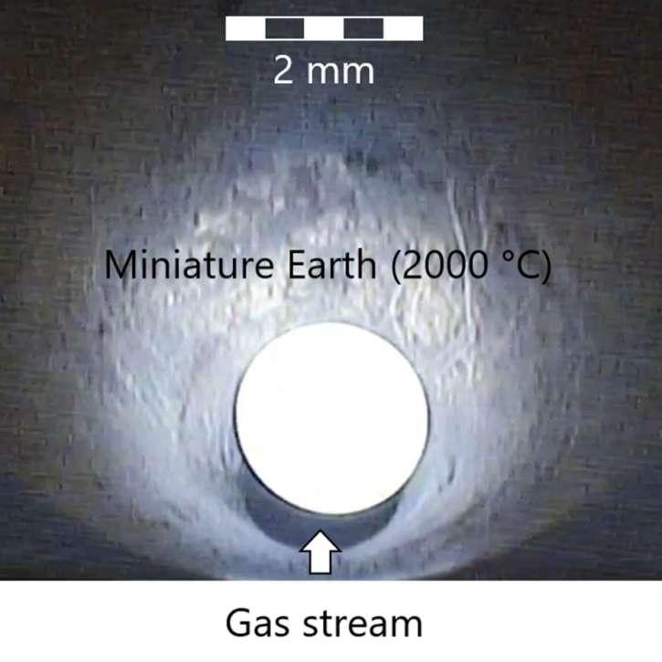 Vue en gros plan de l'expérience avec l'échantillon de magma chaud entouré de gaz et maintenu en suspension. © P. Sossi, ETH Zurich