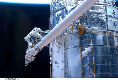 Perché à l'extrémité du bras manipulateur, John Grunsfeld procède au remplacement d'une des batteries de Hubble. A ses côtés, le FGS (capteur de pointage précis). Cliquer pour agrandir. Crédit Nasa