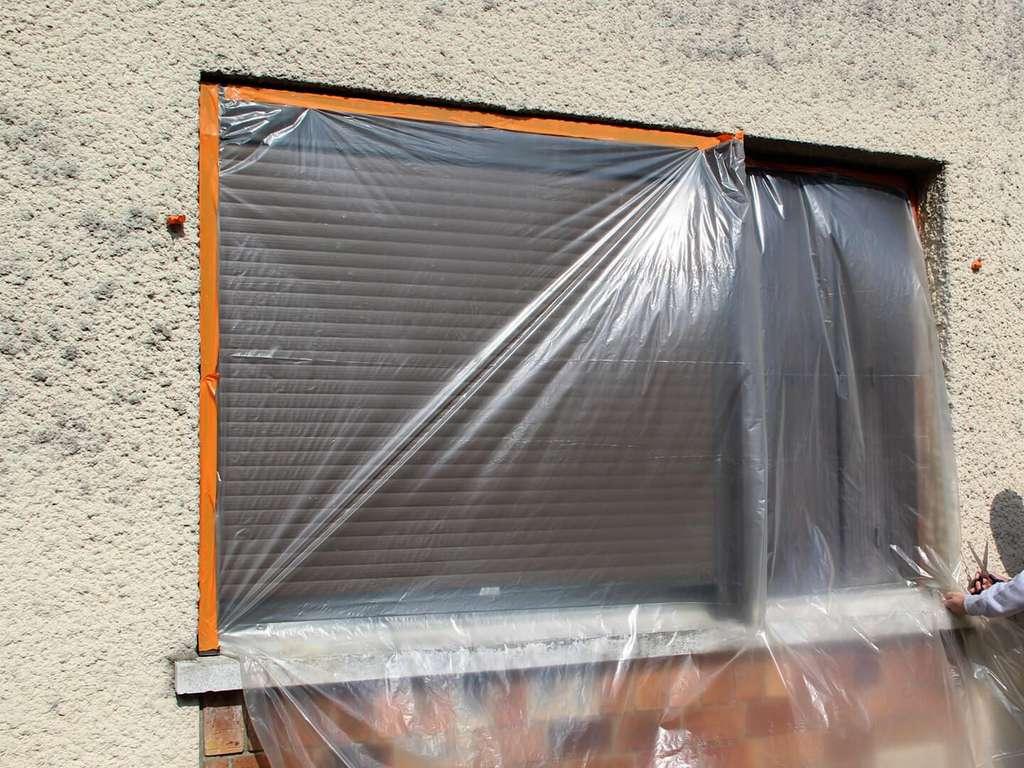 Éloignez, autant que possible, la bâche du vitrage ou du volet afin de ménager un matelas d'air. Utilisez un adhésif spécial résistant à l'humidité pour la fixer. © Weber Façade